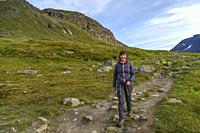 Woman hiking walking down a trail in the mountain area at Kärkkevagge in Kiruna county, Swedish Lapland, Sweden.