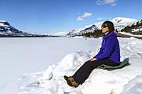 Woman sitting in a snowdrift and enjoying the sun at springtime, Stora sjöfallets nationalpark, Laponia world heritage, Swedish Lapland, Sweden.