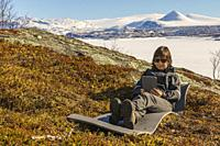 Woman lying down resting in mountain area using her tablett, at Stora sjöfallets nationalpark in spring time with snow around and on the mountains, Sw...