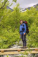 Woman hiking having a backpack on her back crossing a creek on a wooden bridge in Stora sjöfallets nationalpark, Swedish Lapland, Sweden.