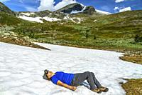 Woman lying down on snow cooling down from the heat in the summer during hiking, Swedish Lapland, Sweden.