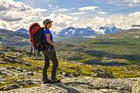 Woman on a mountain with a backpack watching the nice view with mountains in the background, Stora sjöfallets nationalpark, Swedish Lapland, Sweden.