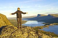 Woman standing on mountain enjoying the view at Stora sjöfallet nationalpark, Swedish Lapland, Sweden.