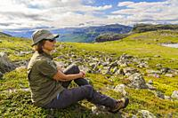 Woman sitting on a mountain enjoying the view, Stora sjöfallet nationalpark, Swedish Lapland, Sweden.