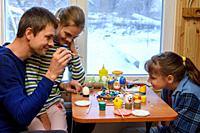 Dad and two daughters paint Easter eggs while sitting at the table by the window.