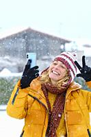 Caucasian young woman enjoying with a mobile phone in snow outdoor in winter time. Navarre, Spain, Europe.