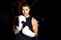 Confident boxer standing in pose and ready to fight. High quality photo.
