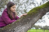 Child girl feeling tree moss over branch. Children discovering textures in nature. Selective focus.