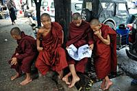 Yangon, Republic of the Union of Myanmar, Asia - A group of Buddhist monks in their saffron robes read a newspaper in downtown Yangon, the former capi...