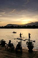 kampot river view in cambodia with SUP stand up paddle boarding tourists at sunset.