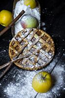 Apple pie with cinnamon on an old textured wooden background.
