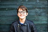 portrait of 12 year old boy with glasses smiling on green wood background dressed in leather jacket.