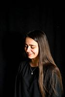 portrait of teenage girl with black background -smiling girl with long hair portrait-.