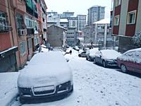 town street and cars covered by snow in winter time after heavy snowfall.
