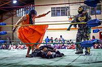 Lucha Libre. Combat between Dina with orange dress and Julieta, cholitas females wrestlers ,with a referee, Sports center La Ceja, El Alto, La Paz, Bo...