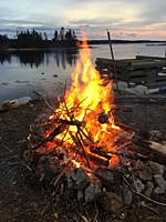 Bonfire at sundown overlooking the sea, Halifax, Nova Scotia. Controlled burning in open air is a common method of disposing of scrap wood, tree limbs...