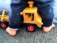 A toddler riding his wooden model truck, Canada.