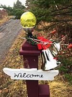 A handcrafted welcome sign at the end of a driveway, Halifax, Nova Scotia. The objects attached to the post, mostly handmade, are typically used as de...