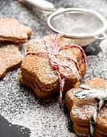 Star shaped baked gingerbread cookies sprinkled with powdered sugar on a black table, close up.
