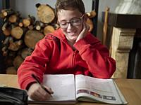 Kid doing is homework at home by the firewood, Ludiente, Castellón, Valencian Community, Spain.