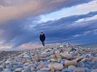 Boy walking on a pebble beach in the Mediterranean sea, Sagunto, Valencia, Valencian Community, Spain.