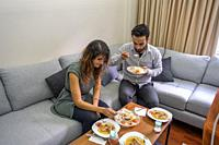 handsome man and beautiful woman have lunch in living room lifestyle concept with copy space.