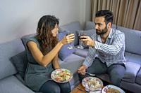 happy couple making a toast and eating their handmade food in their living room interior lifestyle concept.
