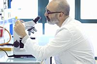 Mature scientist male in his 50s wearing a lab coat looking through a microscope in a laboratory. Basque Country, Spain, Europe.