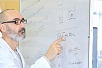 Male teacher in his 50´s in a lab coat explaining chemistry on a blackboard. Basque Country, Spain, Europe.