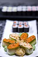 set of sushi rolls with seafood on a black stone background.