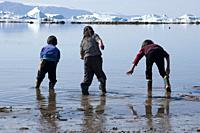 Qaanaaq, Greenland. Kids playing in the shallow water of the sea. .