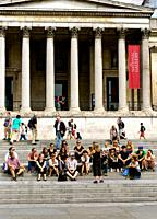 Visitors with guide outside the National Gallery. London trafalgar square.