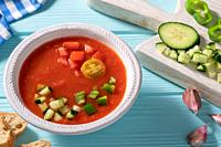 Gazpacho Andaluz is an Andalusian tomato cold soup from Spain with cucumber, garlic, pepper on light blue background.
