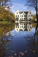 Castle Staverden reflecting in the moat and surrounded by autumn colored trees.