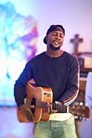 talented African man feeling his inner creativity and passion, playing acoustic guitar