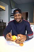 African man eating orange in kitchen