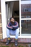 optimistic African man sitting in window of his flat in Leeuwarden, Friesland, Netherlands