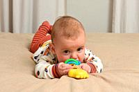 baby lying on the bed playing with a toy,.
