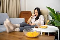 one young lady sits on couch and laughs at something on book by extending her leg in living room with crisps, cookies and tea home interior copy space...