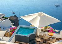 Santorini. Terraces on the high shore of Thera Island. Swimming pool and loungers for relaxing in sunny weather. Yachts by the shore.