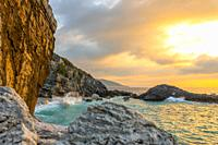 Summer evening and a small beach on a rocky beach. Wave smashes on coastal rocks with lots of splashes.