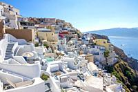 Greece. Sunny summer day in Santorini. White houses in the city of Oia on the caldera and sea views.