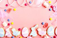 Candies and Easter frosted cookies in shape of egg chicken and rabbit on pink background. Flat lay mockup with copy space.