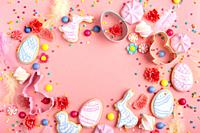 Sugar sprinkles, candies, Cookie cutters, Easter frosted cookies in shape of egg chicken and rabbit on pink background. Flat lay mockup with copy spac...