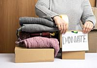 woman in a gray sweater is packing clothes in a box, the concept of assistance and volunteering, donation.