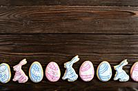 Easter frosted cookies in shape of egg, rabbit and chicken on wooden background. Flat lay with copy space.