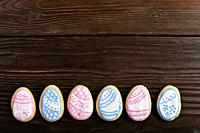 Easter frosted cookies in shape of egg on wooden background. Flat lay with copy space.