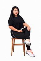 Latin woman wearing sportswear sitting sideways and legs crossed on white background.