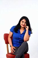 latin american woman sitting on a chair looking at camera on white background.
