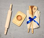 spoon and spatula tied with blue ribbon on gray background and wooden rolling pin, top view.